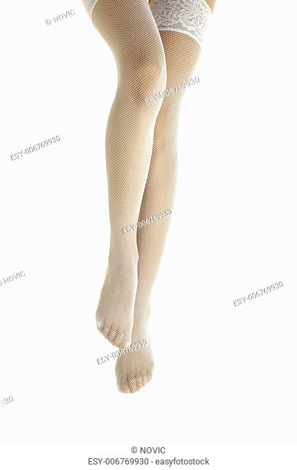 Close-up photo of the elegant woman legs in white stockings