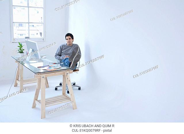 Man sitting at computer with his feet up