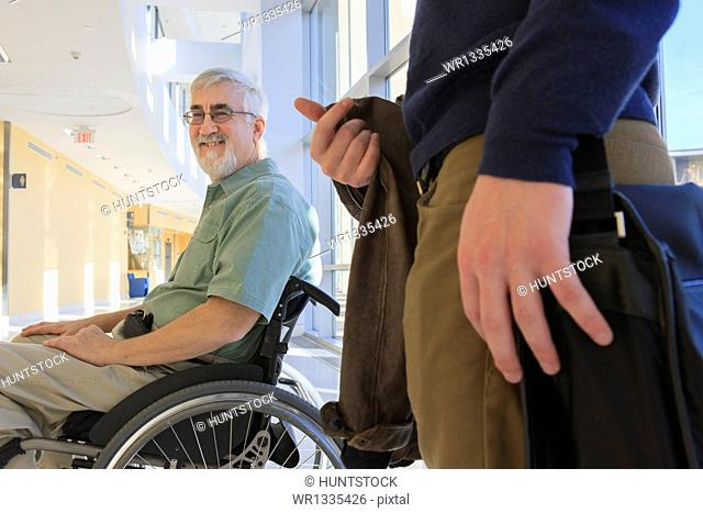 Professor with Muscular Dystrophy in a university hallway with a student
