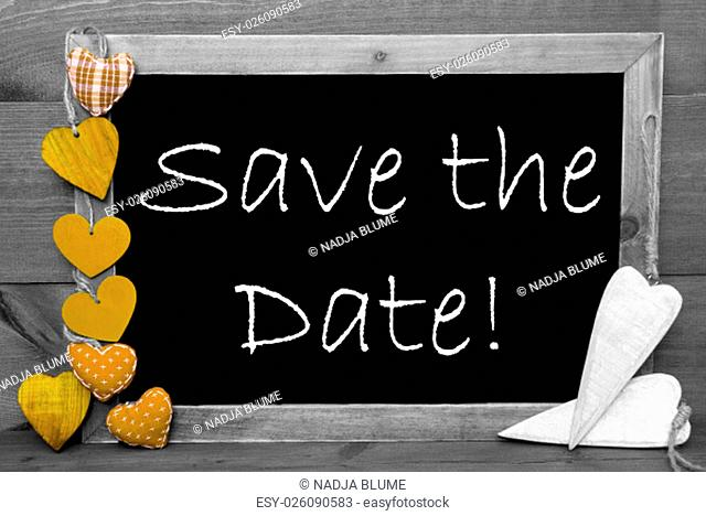Chalkboard With English Text Save The Date And Yellow Hearts. Wooden Background With Vintage, Rustic Or Retro Style. Black And White Image With Colored Hot...
