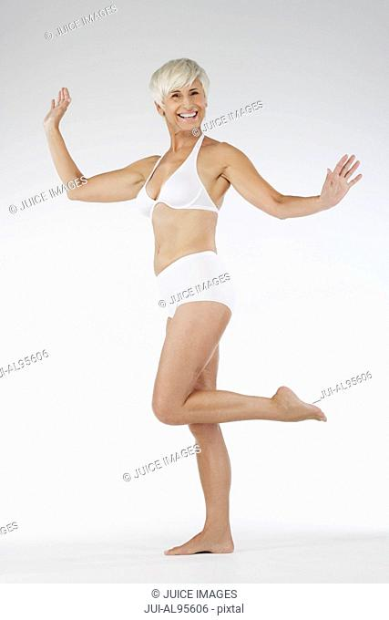 Happy senior woman in undergarments showing weight loss