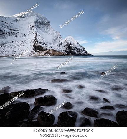 Winter mountain peaks rise over Bunes beach, Moskenesøy, Lofoten Islands, Norway