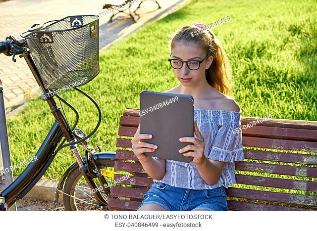 Girl sitting on park bench playing with tablet pc and bike