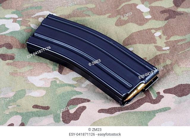 US ARMY M-16 rifle magazine with cartridges on camouflage uniform background