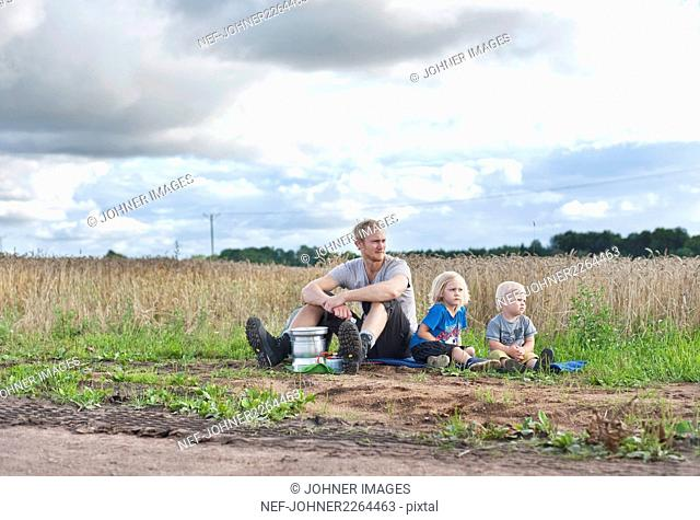 Father with children sitting near field