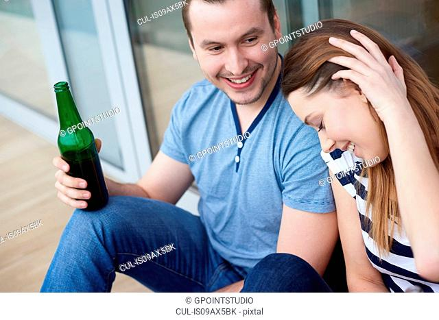 Young couple sitting outdoors, drinking bottled beer