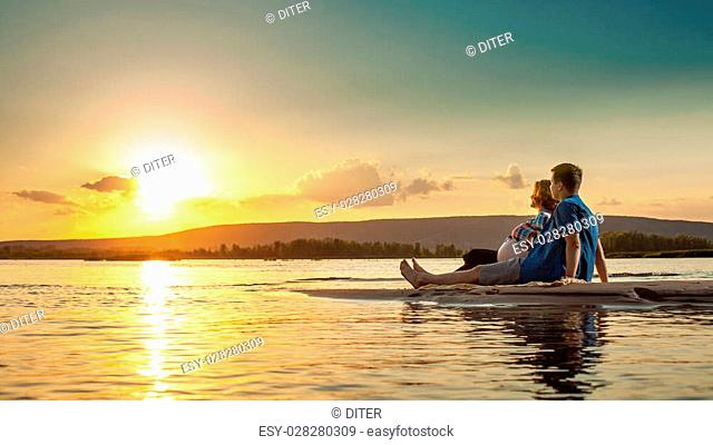 Beautiful couple is sitting on the beach and looking at the sunset