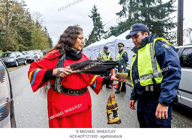 RCMP Officer shares Indigenous womans sage smudge offering, Blockade of Kinder Morgan Pipeline entrance, Burnaby Mountain, Burnaby, British Columbia, Canada