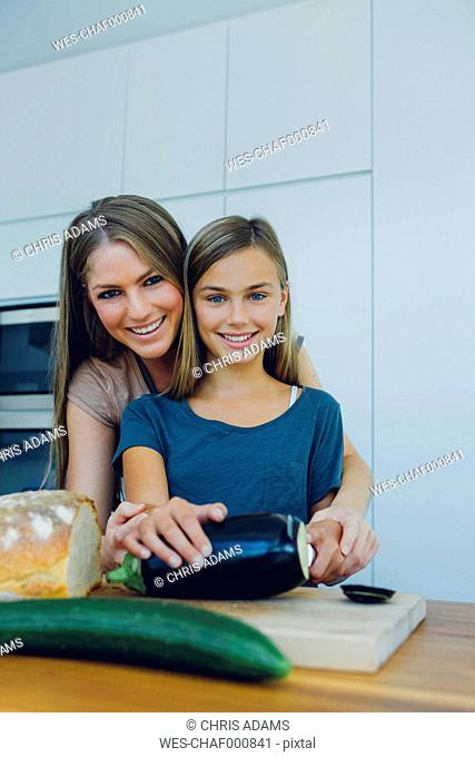 Mother and daughter in kitchen preparing healthy food