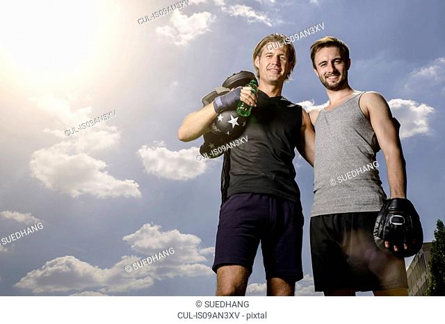 Portrait of male boxer and personal trainer in park