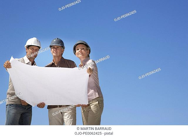 Couple reviewing blueprints with architect