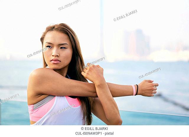 Young woman exercising arms and shoulder on waterfront, Hong Kong