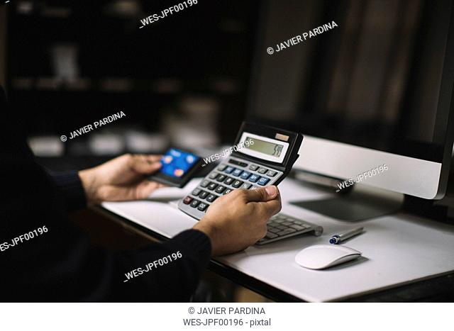 Man using calculator and credit card at desk, partial view