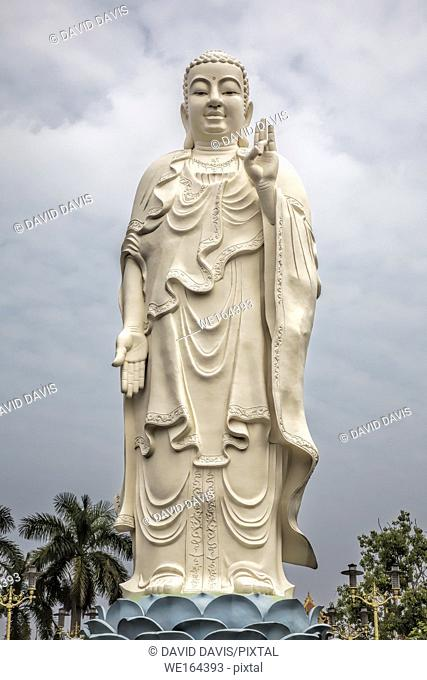 Standing Buddha statue at the Vinh Trang Temple in Mytho City, Mekong Delta, Vietnam