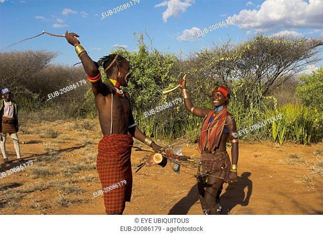 Hama Jumping of the Bulls initiation ceremony. Man whipping women on back in ritual flogging. The whip is made of rope or reed bushes