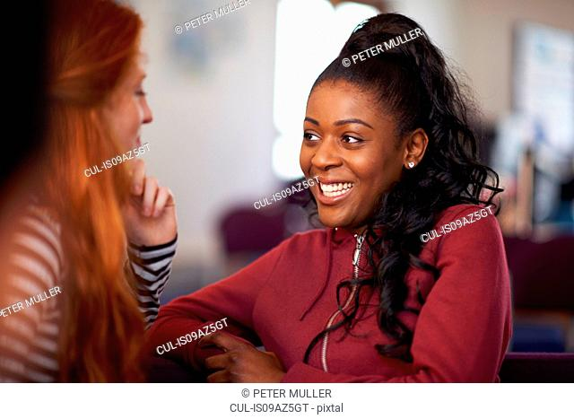 Two female students gossiping in common room