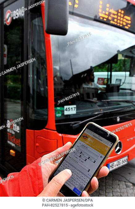 ILLUSTRATION - A young woman holding her smartphone in front of a bus of the public transport organisation BSAGEin Bremen, Germany, 5 August 2016