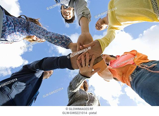 Low angle view of university students stacking their hands in a huddle