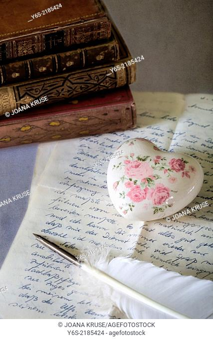 a quill on an old letter with books