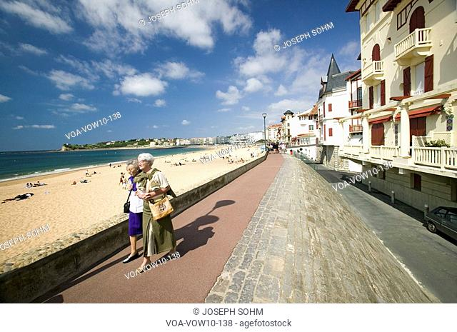 Two women walk down beach boardwalk at St. Jean de Luz, on the Cote Basque, South West France, a typical fishing village in the French-Basque region near the...