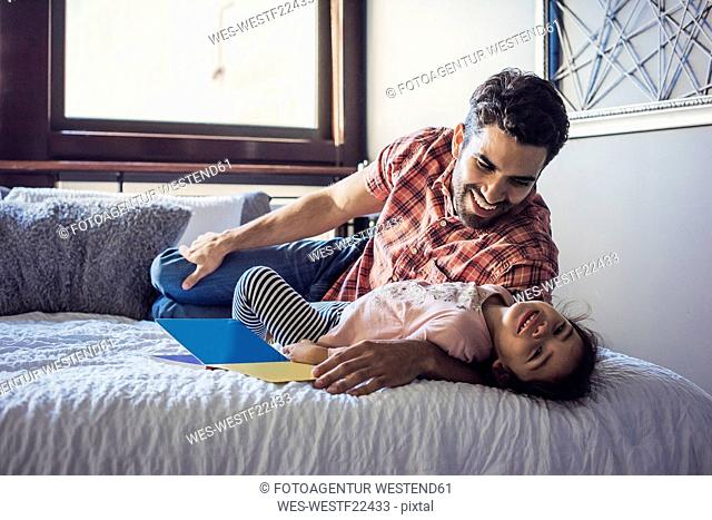 Father and daughter playing on bed