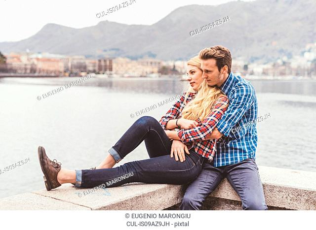 Romantic young couple sitting on harbour wall, Lake Como, Italy