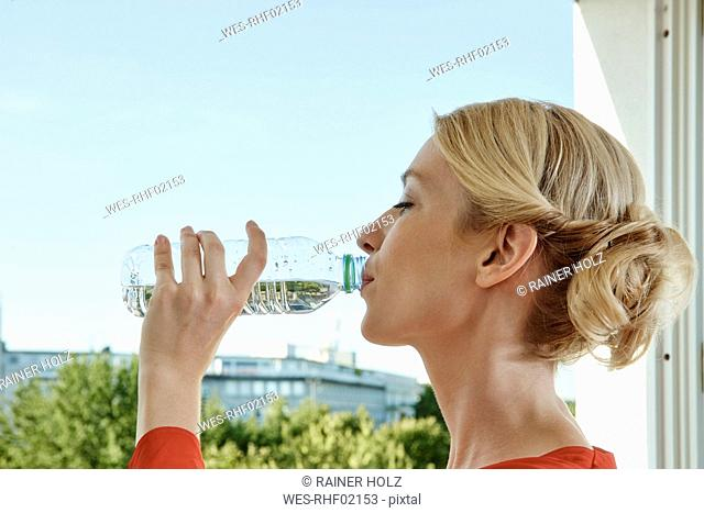 Young woman drinking water from bottle at the window