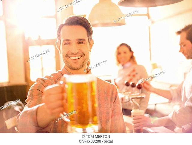 Portrait smiling man toasting beer stein in bar