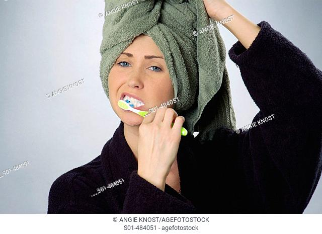 Young woman, age 20-25, brushing her teeth, holding green towel on her head, wearing black bath robe.  Left side of photo includes space for possible insertion...