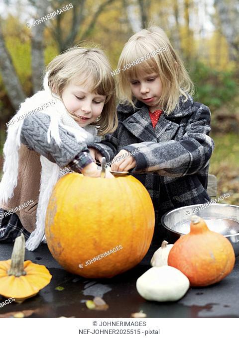 Girls preparing pumpkin