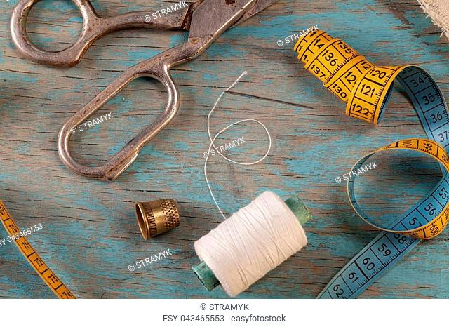 Retro sewing accessories - scissors, tape measure, thread on blue wooden background