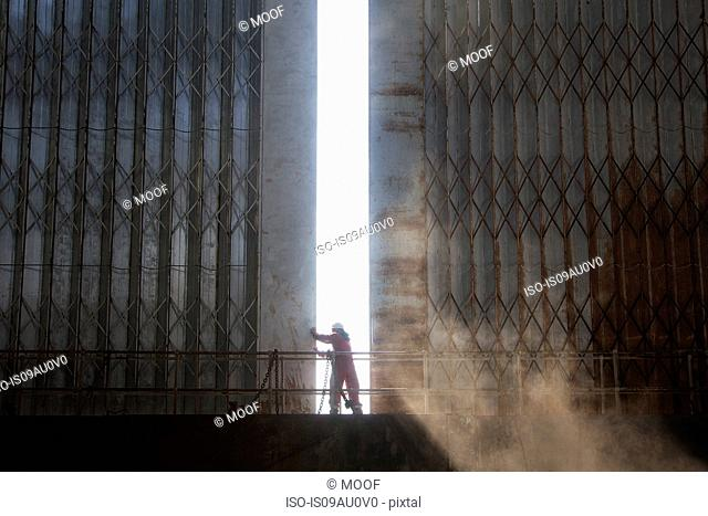 Silhouetted worker opening shipyard doors in morning sunlight