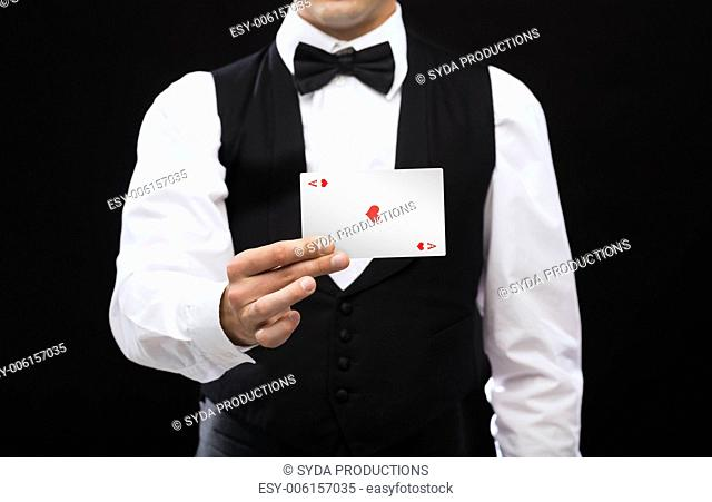 magic, performance, circus, casino and show concept - casino dealer holding white card