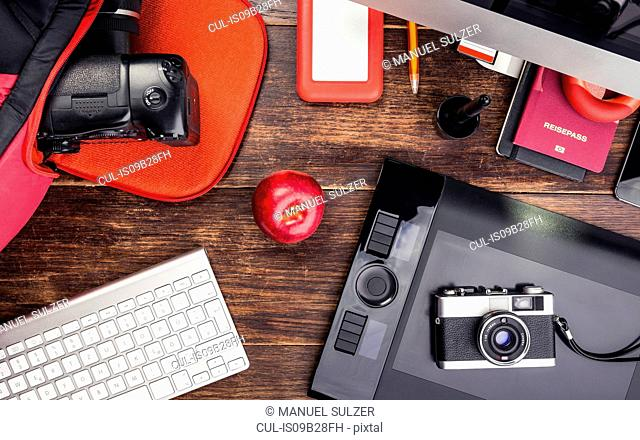 Overhead view of photo editing equipment; graphic tablet, retro camera, digital camera and computer keyboard