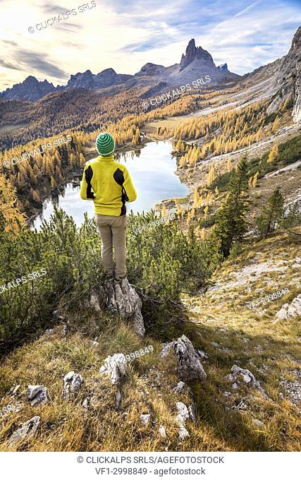 Hiker admiring the autumn colors at Federa lake, Cortina d Ampezzo, Belluno, Dolomites, Veneto, Italy