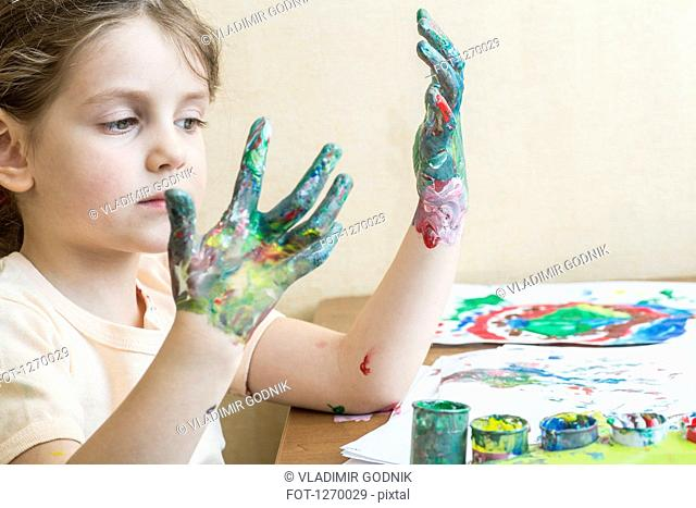 Girl looking at her painted hands