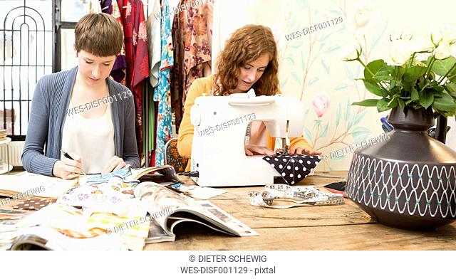 Two female fashion designers working together at their studio