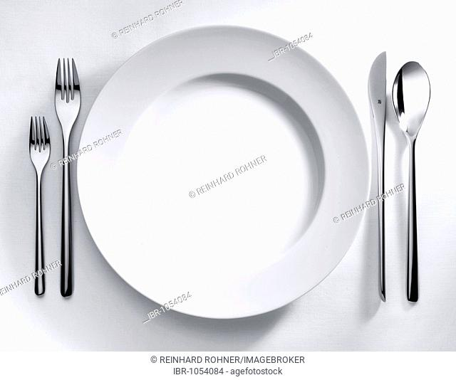 Plate and cutlery on a white tablecloth
