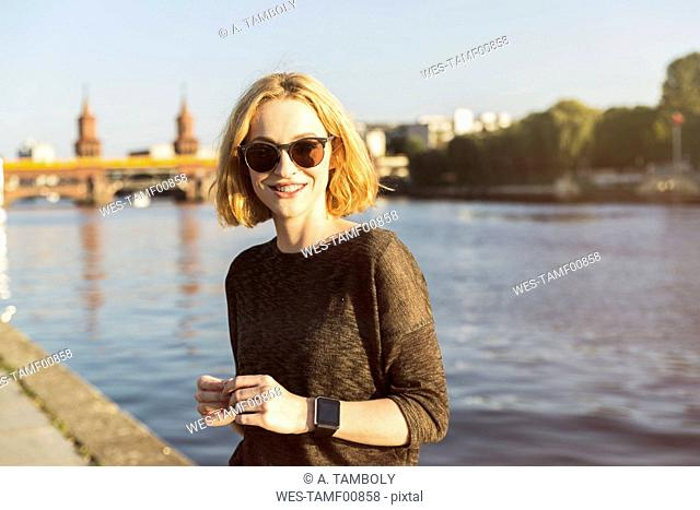 Germany, Berlin, portrait of smiling young woman wearing sunglasses and smartwatch