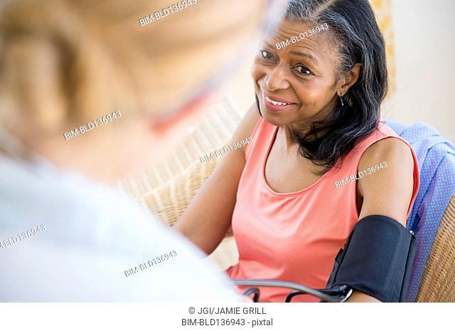 Woman having blood pressure taken on sofa