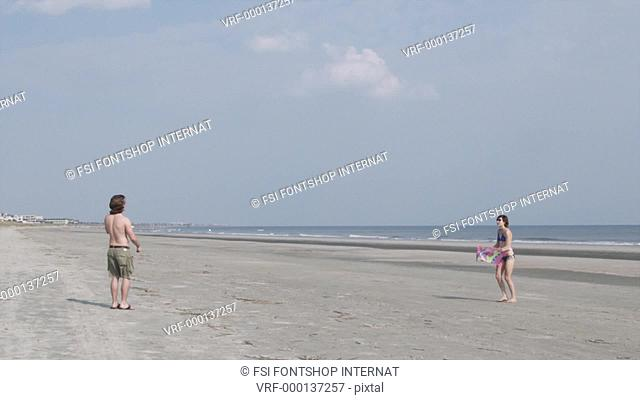 SLO MO, MS, Lockdown of a young couple flying a kite on a beach