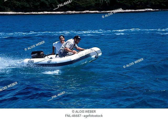 Two men on rubber boat in water, Susak, Istrien, Kvarner Bay, Croatia