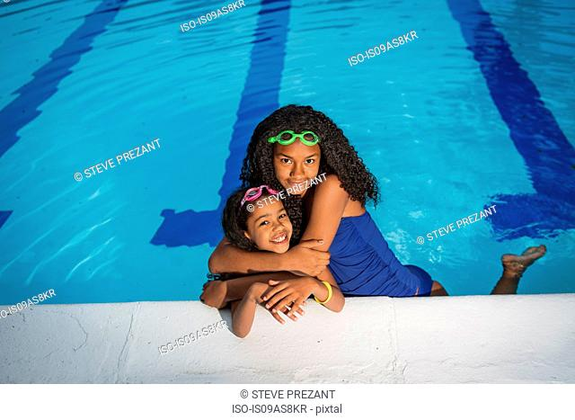 Girl in swimming pool with arms around little sister, looking at camera smiling