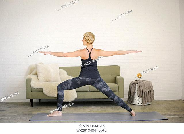 A blonde woman in a black leotard and leggings on a yoga mat, her legs apart and arms outstretched