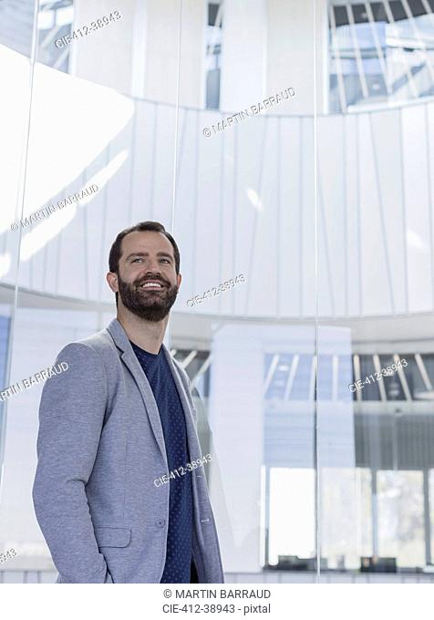 Portrait smiling, confident businessman in office atrium