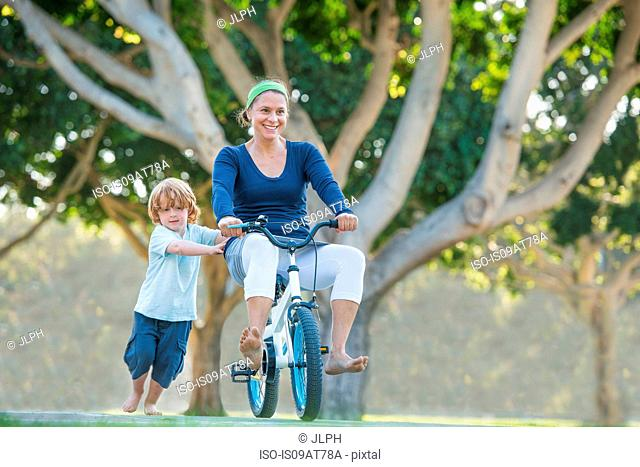Mother sitting on son's bike, son pushing her along