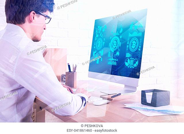 Side view of young businessman using computer with bitcoins on screen in modern office. Finance and internet concept. Double exposure