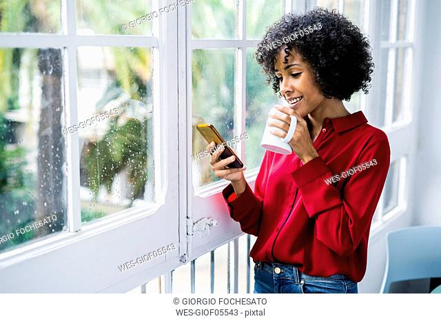 Smiling woman with cup of coffee and cell phone standing at the window at home
