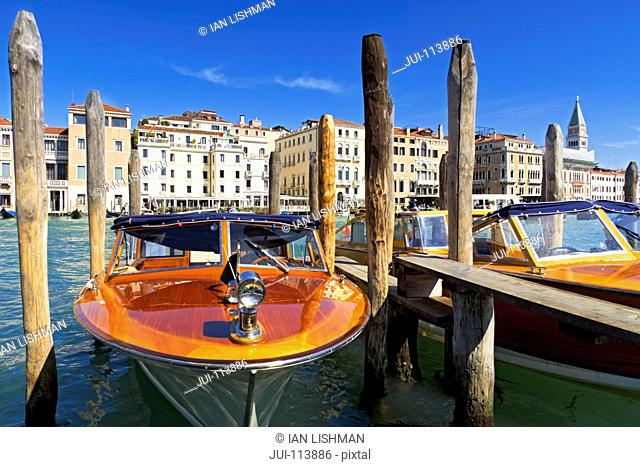 Wooden water taxi boats moored on sunny Grand Canal in front of San Marco Campanile and architectural buildings in Venice, Italy