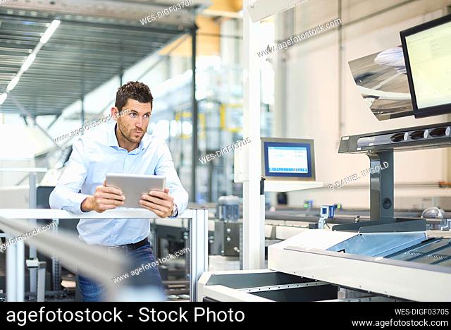 Businessman with tablet looking at machine in modern factory